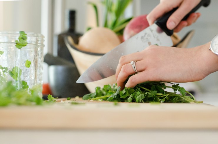 Close-up of woman's hand chopping fresh herbs. with kitchen knife.