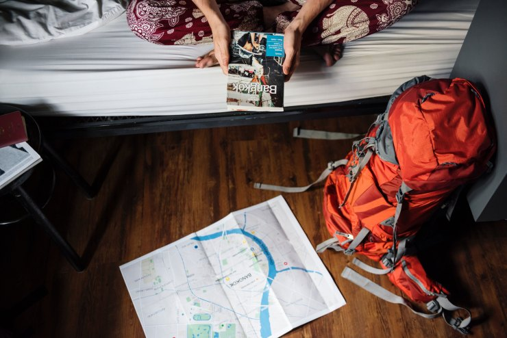Person reading guidebook on bed with backpack and map on floor