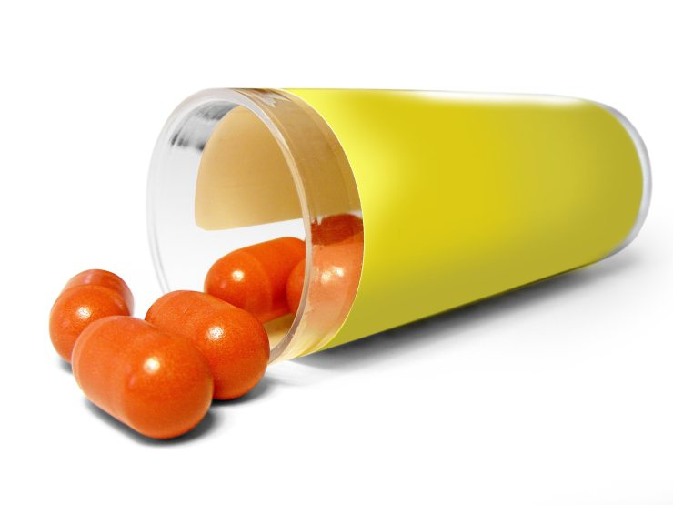 Yellow pill canister with orange oval pills spilling out.